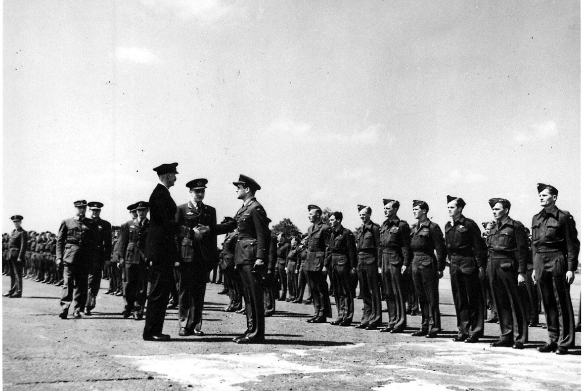 Militærtropp oppstilt på en åpen plas under inspeksjon av Kong Haakon VII og Kronprins Olav. Kong Haakon hilser på en offiser.