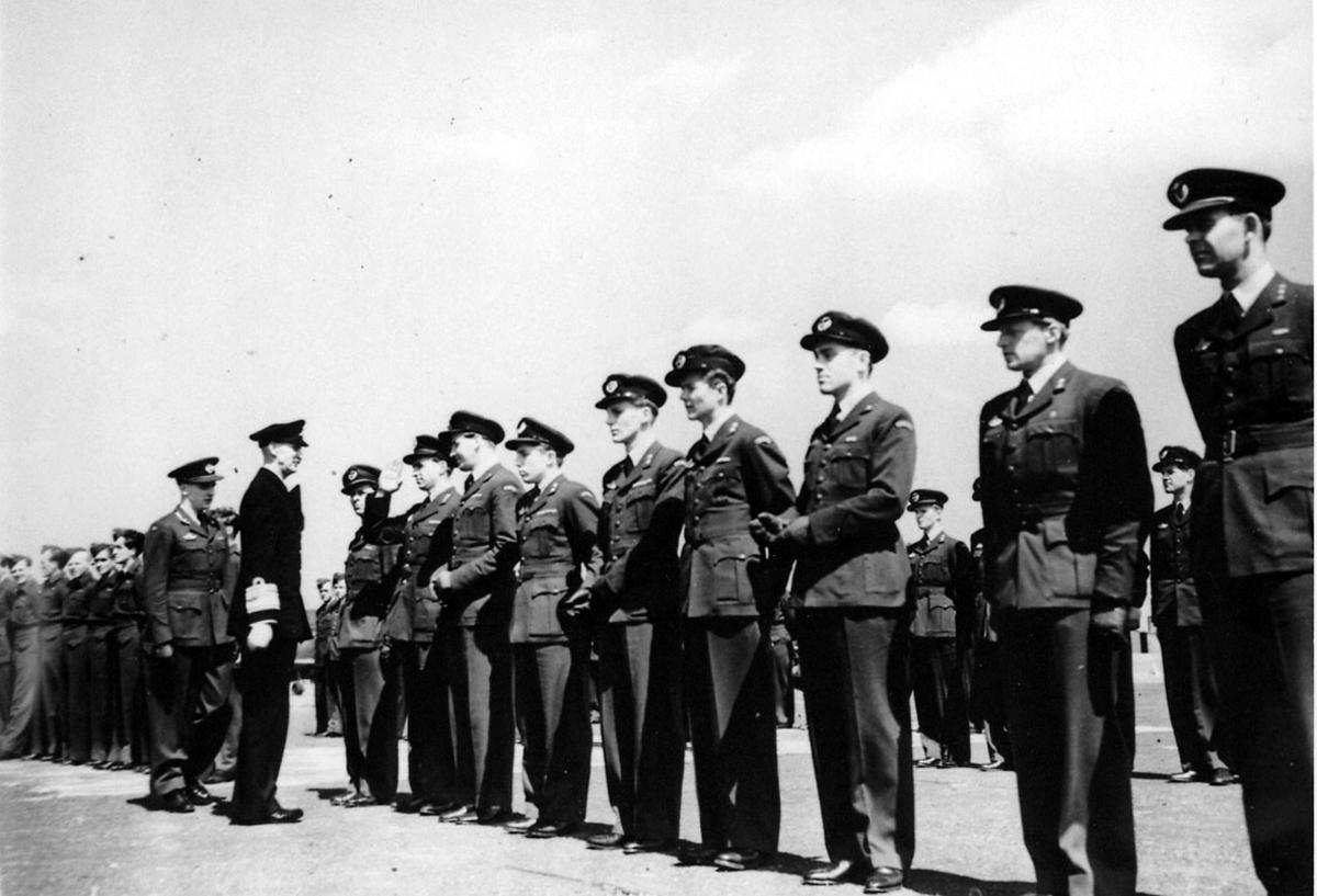 Militærtropp oppstilt på en åpen plas, under inspeksjon av Kong Haakon VII.