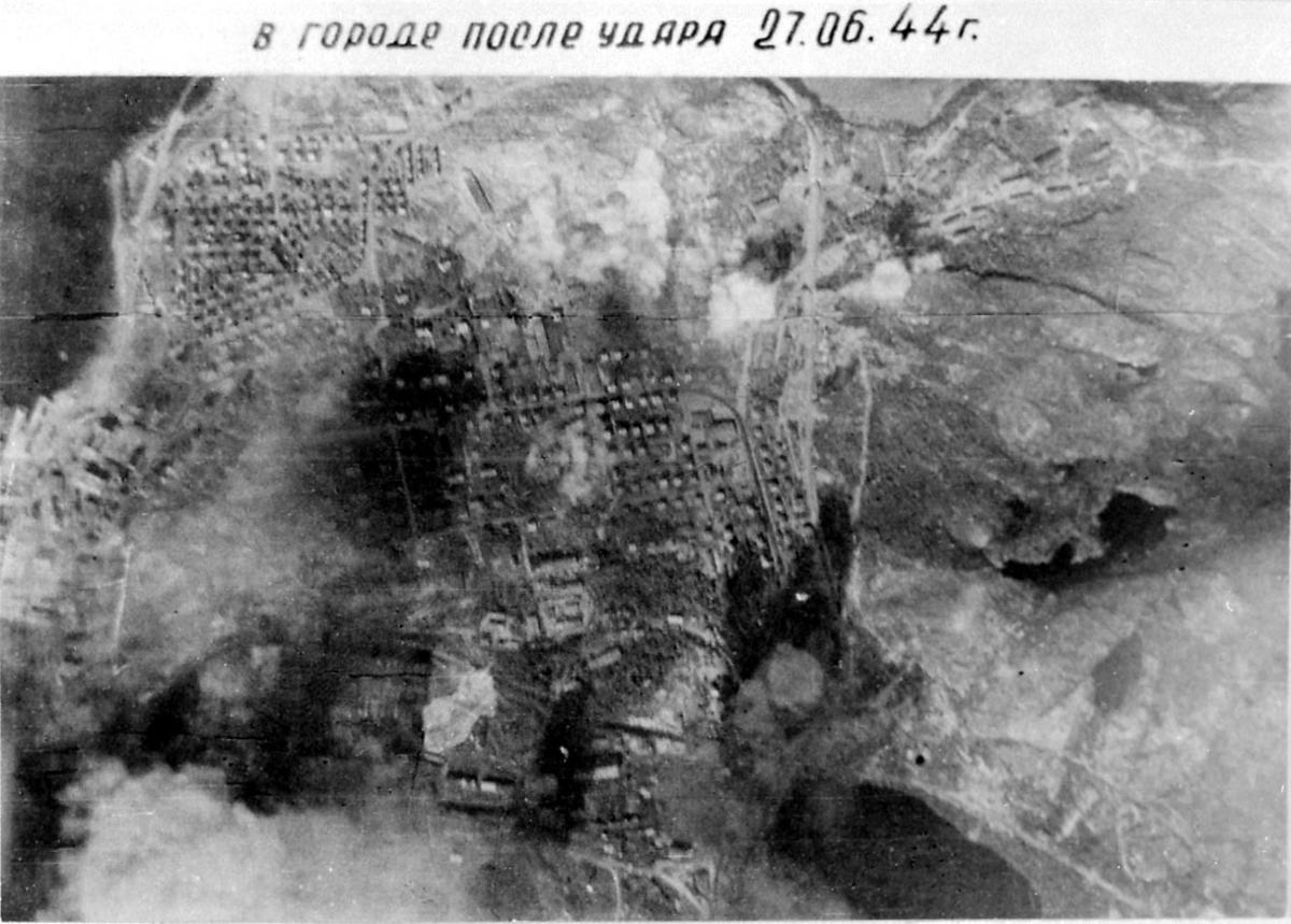 Luftfoto, tettsted med noe røyk/brann som stiger opp. Noe russisk tekst på bildet.