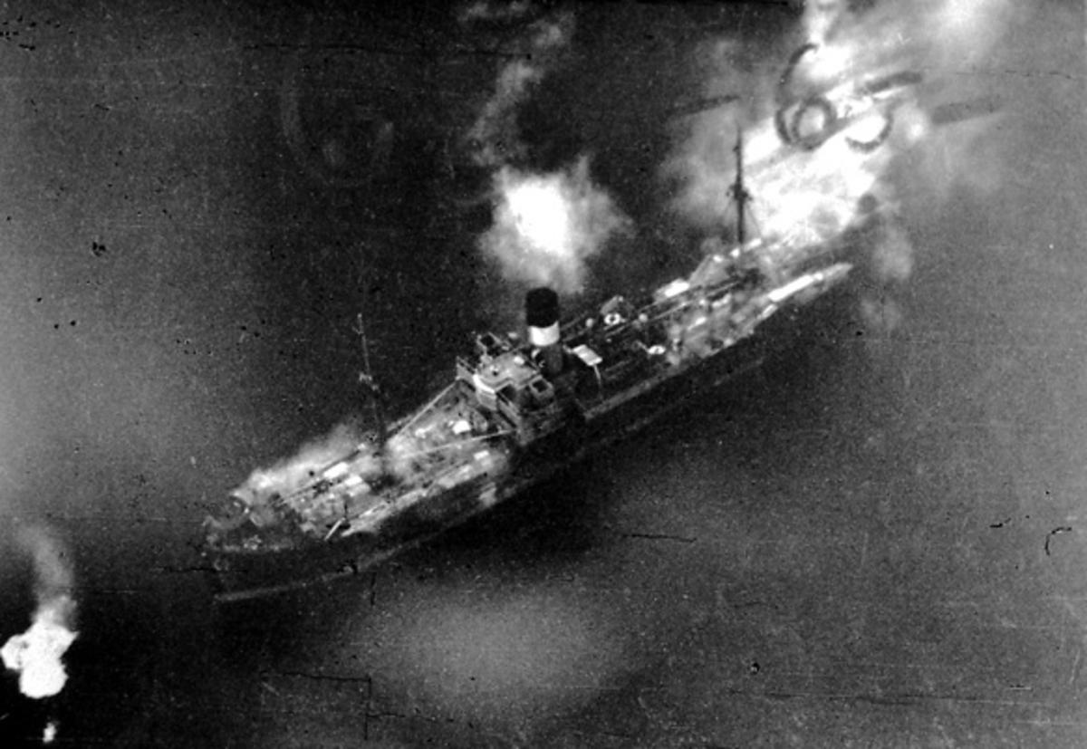 Luftfoto. Fartøy nedenfor. Hav rundt. Røyk stiger opp fra fartøyet etter bombeangrep.
