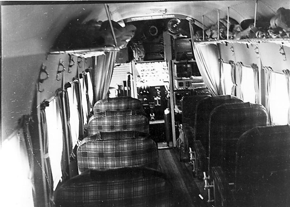 Flyinteriør, Junkers JU 52. Inne i flycabinen, tomme seter, bagasjehyller under taket.