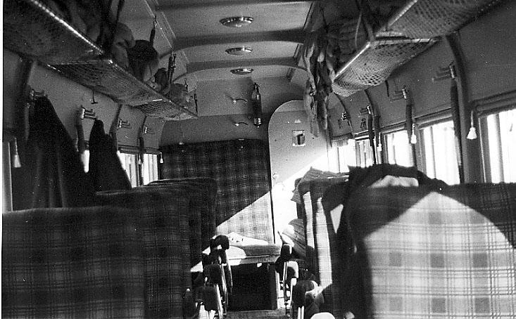 Flyinteriør. Flycabinen med tomme seter, sett fra midtgangena. Bagasjehyller på begge sider, under taket.