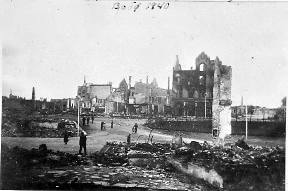 Bodø i ruiner etter bombingen under 2. verdenskrig. Flere personer i gata.
