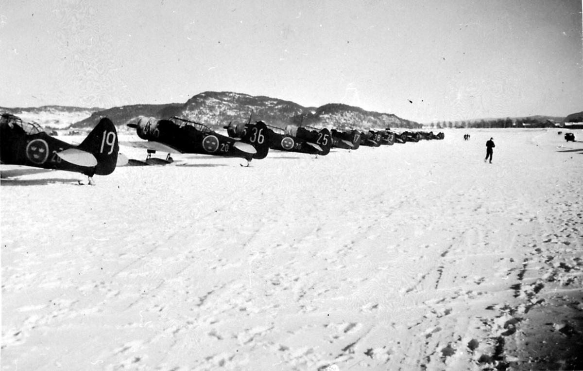 Lufthavn, 12 fly på bakken, Harvard, fra den svenske 20 skv.  Flere personer på rullebanen. Snø på bakken.