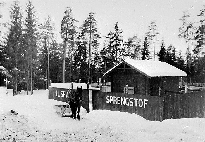 "Lufthavn. Lita bygning med bl.a. påskrift ""sprengstof"". 1 person med hest og slede foran. snø på bakken."