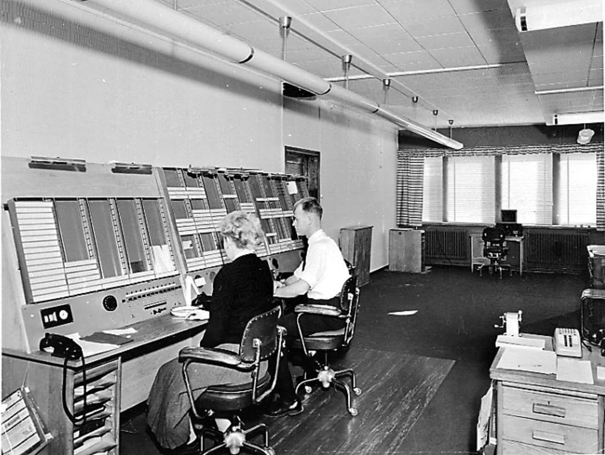Lufthavn. Interiør fra kontrollsentralen. 2 personer ved kontrollpulten.