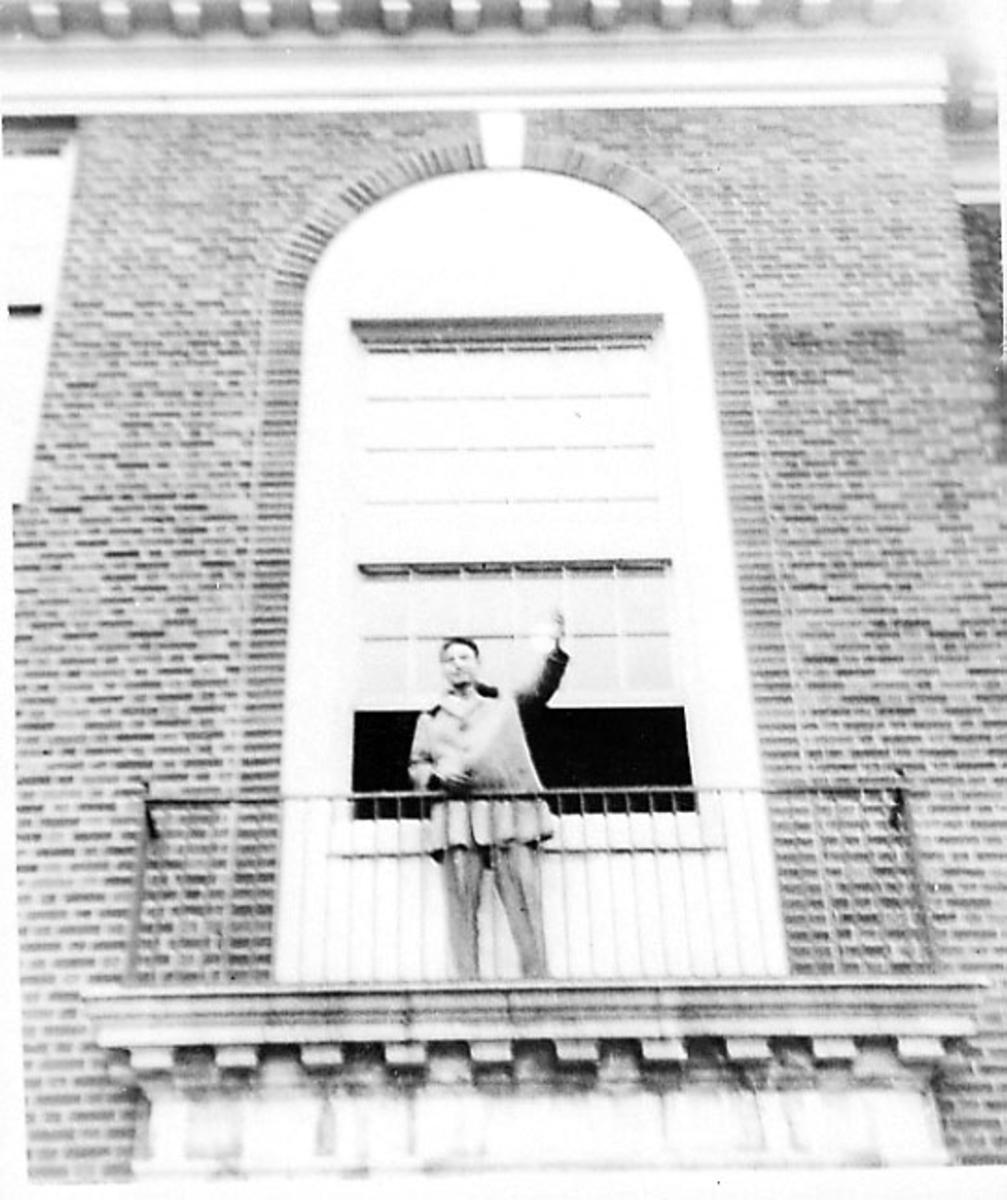 Portrett. 1 person på en veranda til ei større bygning, E.R.H.S (sivil skole).