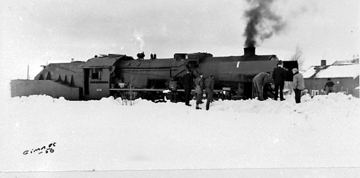 1 lokomotiv - tog. Noen personer. Snø på bakken.