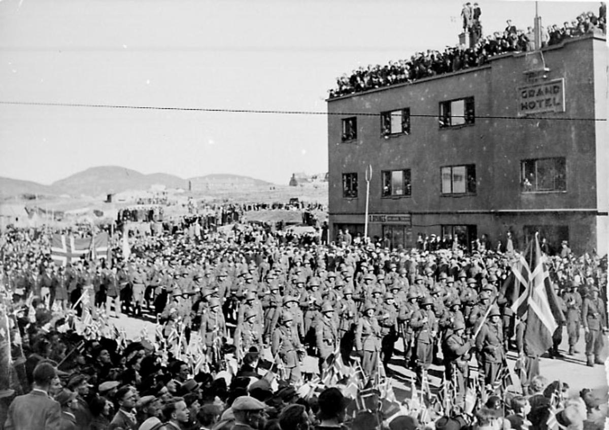 By, større folkemengde samlet i gatene - flere av dem er soldater som masjerer. Bak sees Grand Hotell med mange personer på taket.