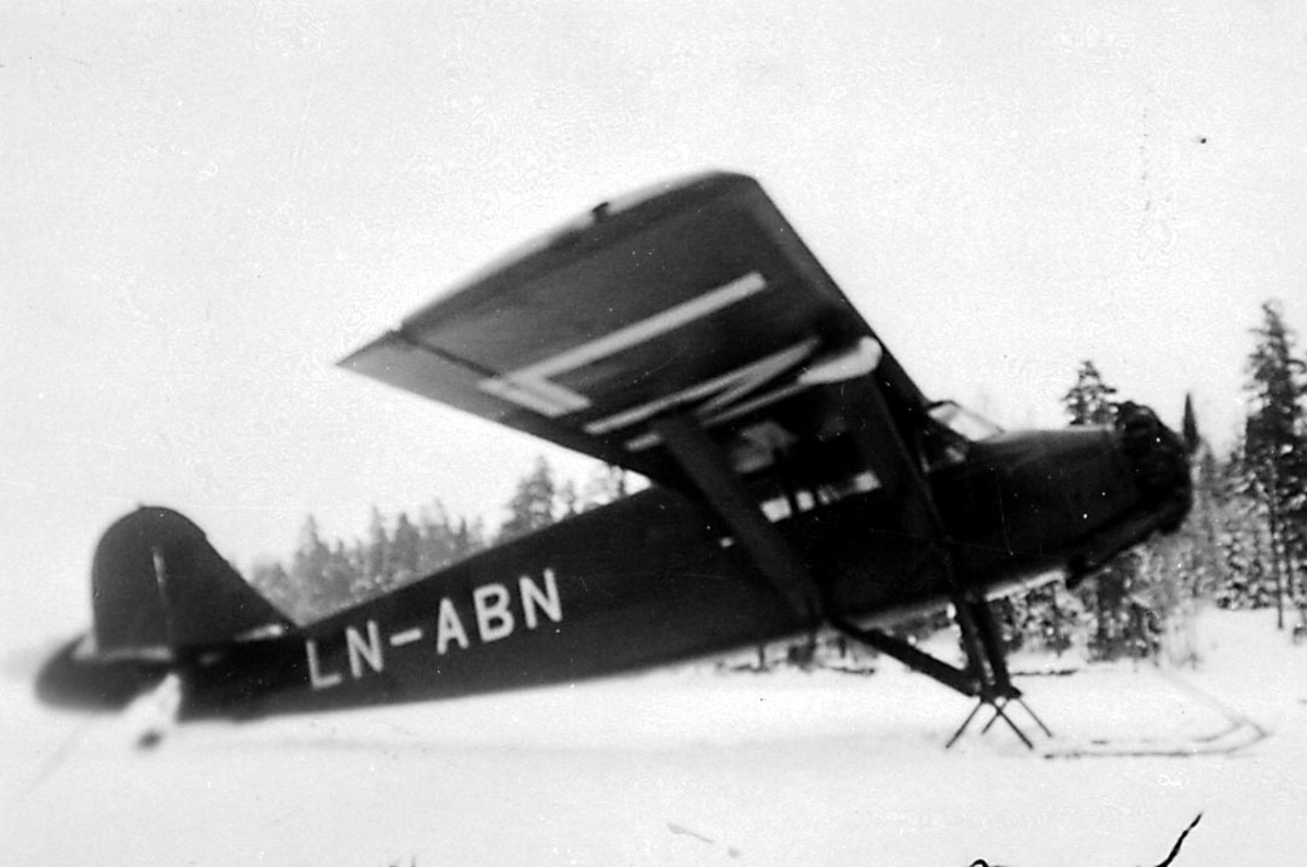 1 fly på bakken med ski på snø, Stinson SM-IF, LN-ABN fra Norsk Lufttrafikk.