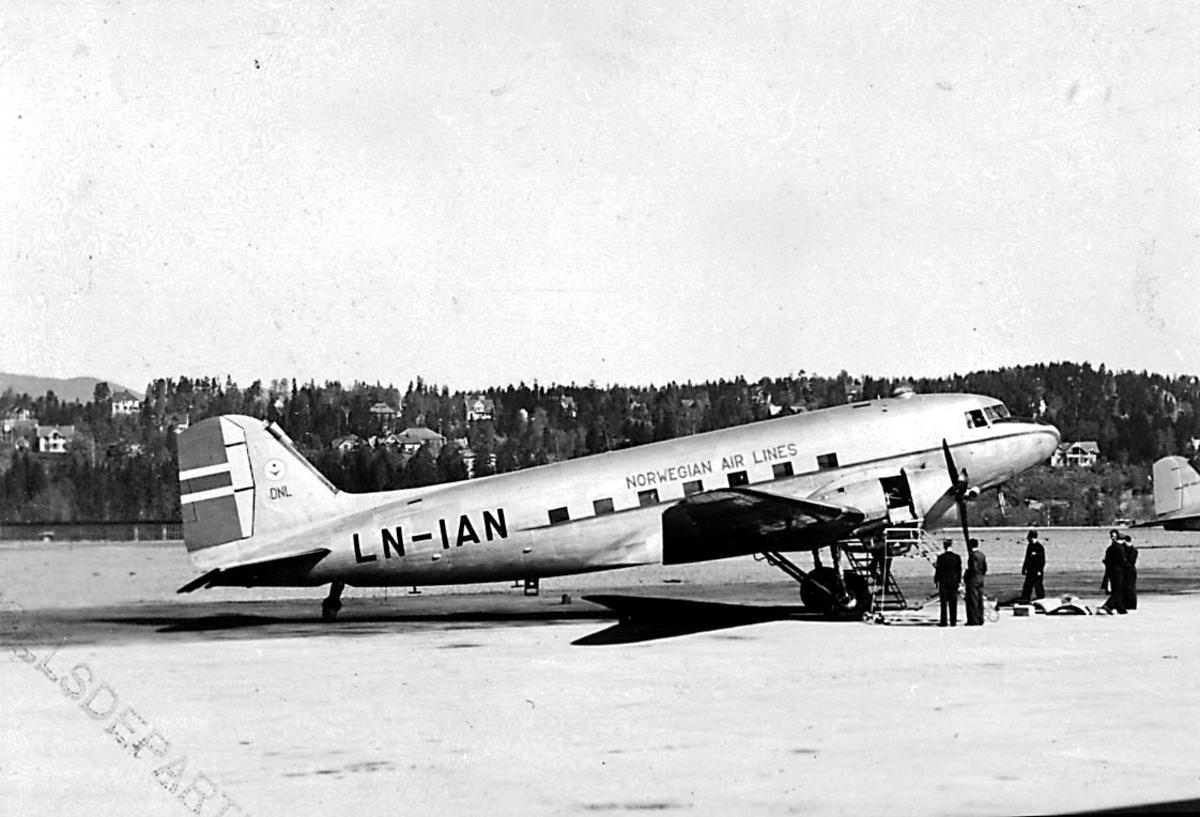 "Lufthavn, 1 fly på bakken, Douglas DC-3 C-47A-90-DL, LN-IAN ""Nordvind/ Gunnar Viking"" fra Staten v/Forsvarsdepartementet. Flere personer ved flyet."