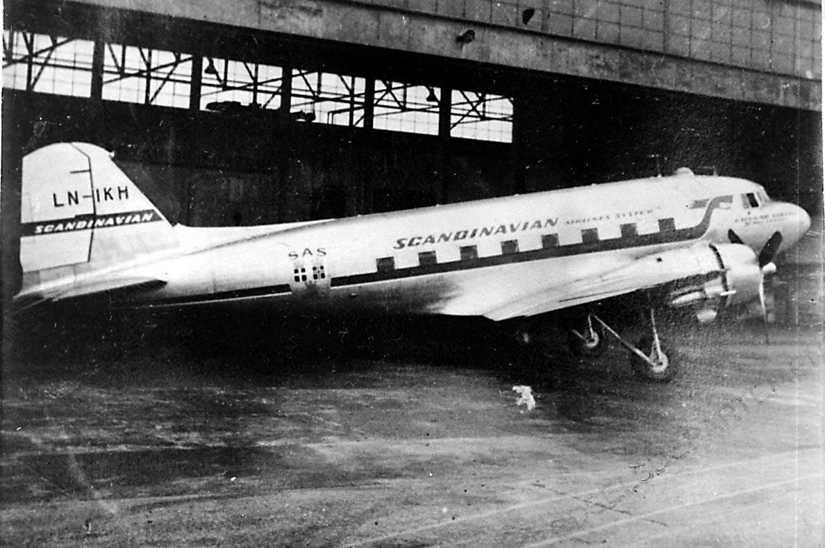 """Lufthavn, 1 fly på bakken foran 1 hangarbygning, Douglas DC-3 /C-47 Dacota, LN-IKH """"Hallvard Viking"""" fra DNL A/S Oslo."""