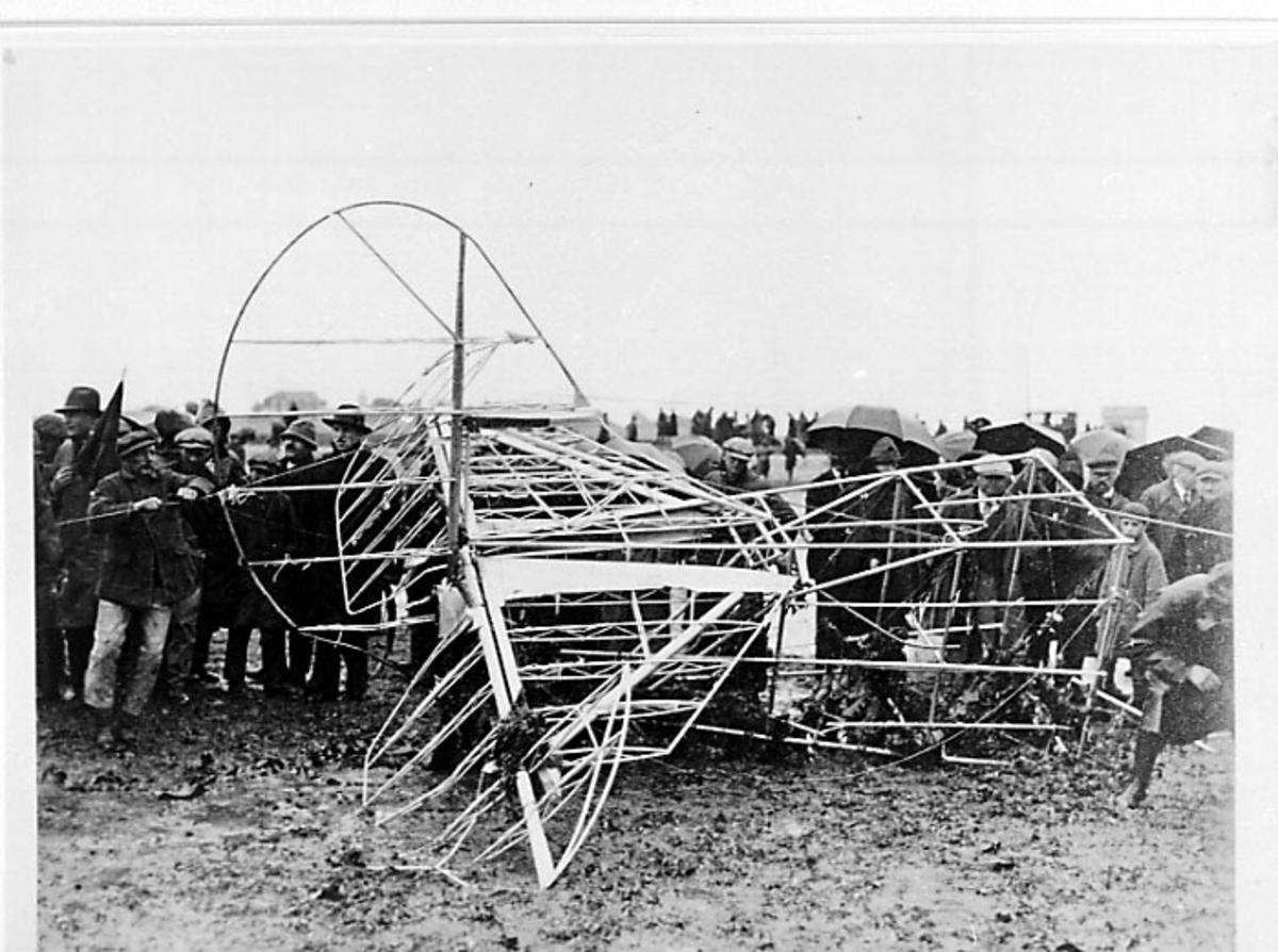 """Flydel ligger på land, bærekonsttruksjon til haleparti, Fokker C-2, C-2A """"America"""". Bruker: Admiral Byrd. Større folkemengde rundt."""