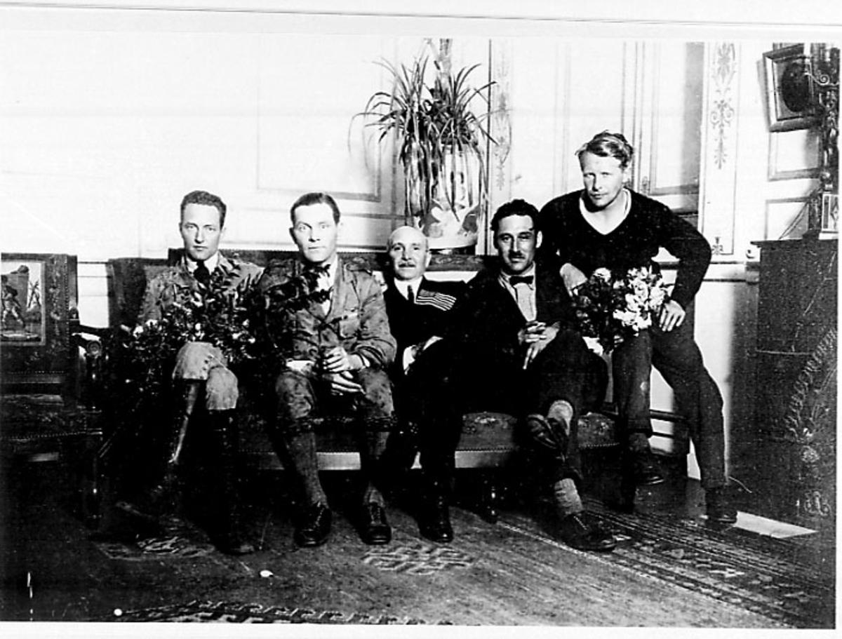 Portrett, 5 personer sitter på en benk, noen med blomster i hendene. Tatt innendørs.