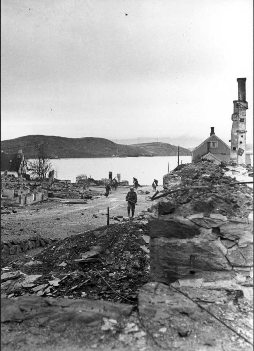 By - tettsted. Vei med noen personer, menn i militæruniform. Ruiner av flere bygninger. Hav - havneområde i bakgrunnen. Tyske soldater, hjertøya i bakgrunn.