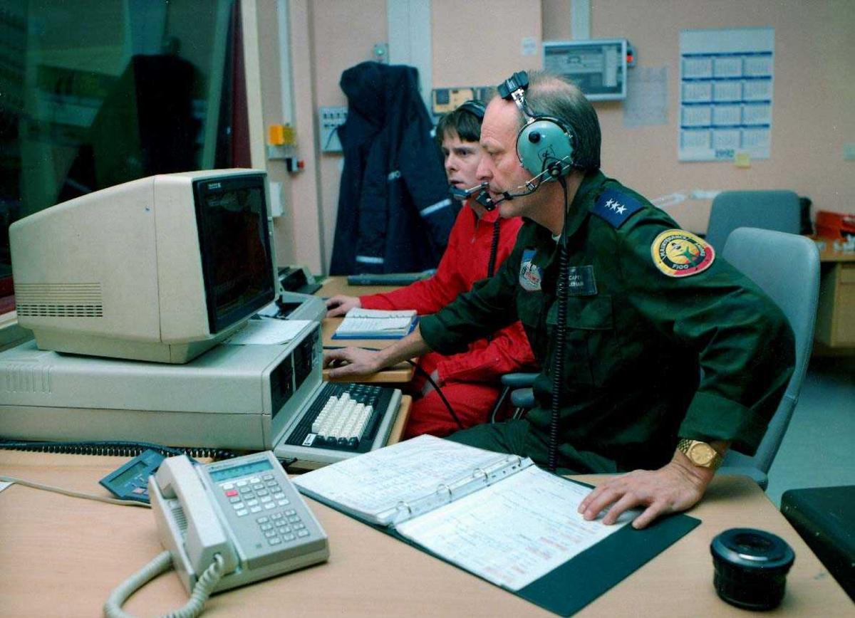 Lufthavn-flyplass.     To personer, en i uniform inne i kontrollrom motorprøvehus.