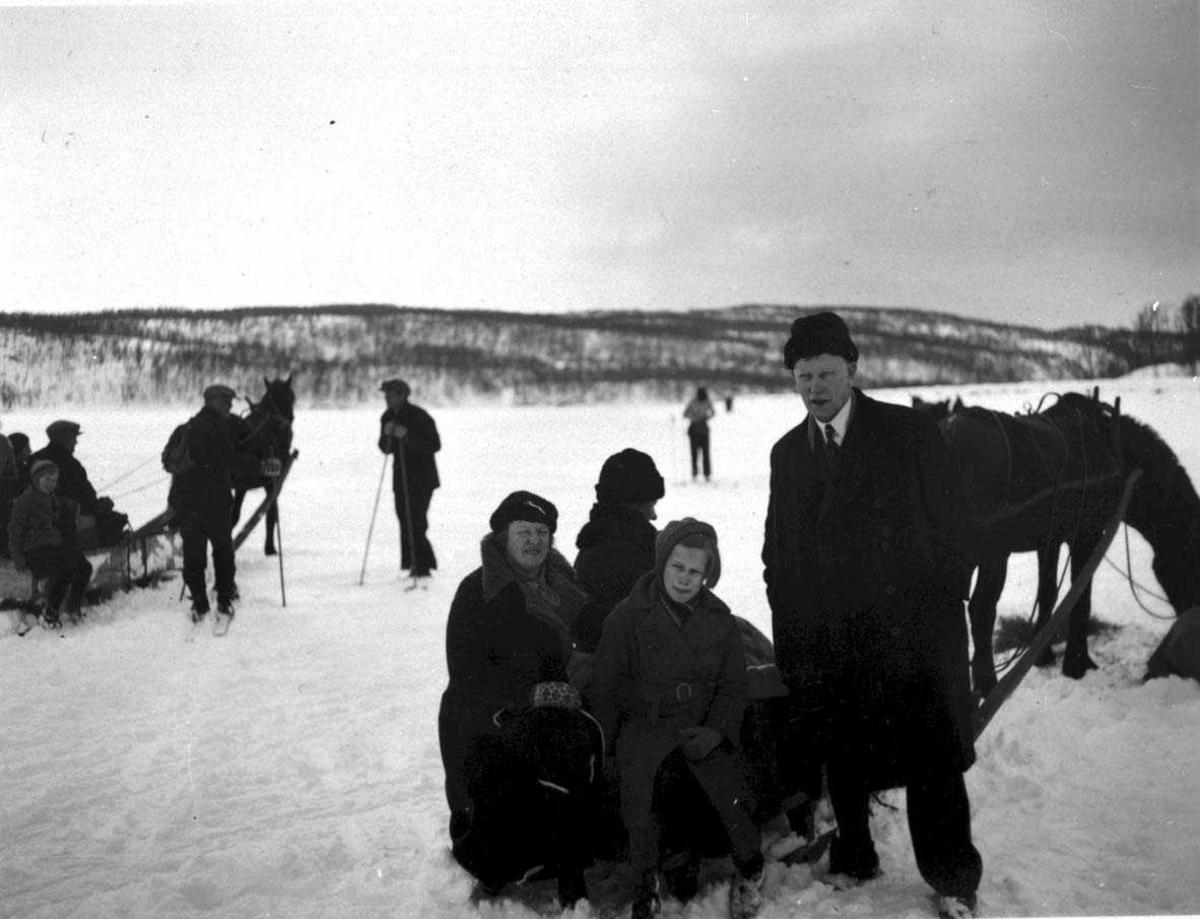 Gruppebilde. Kvinner, menn og barn ved 2 hester med slede. Snø på bakken
