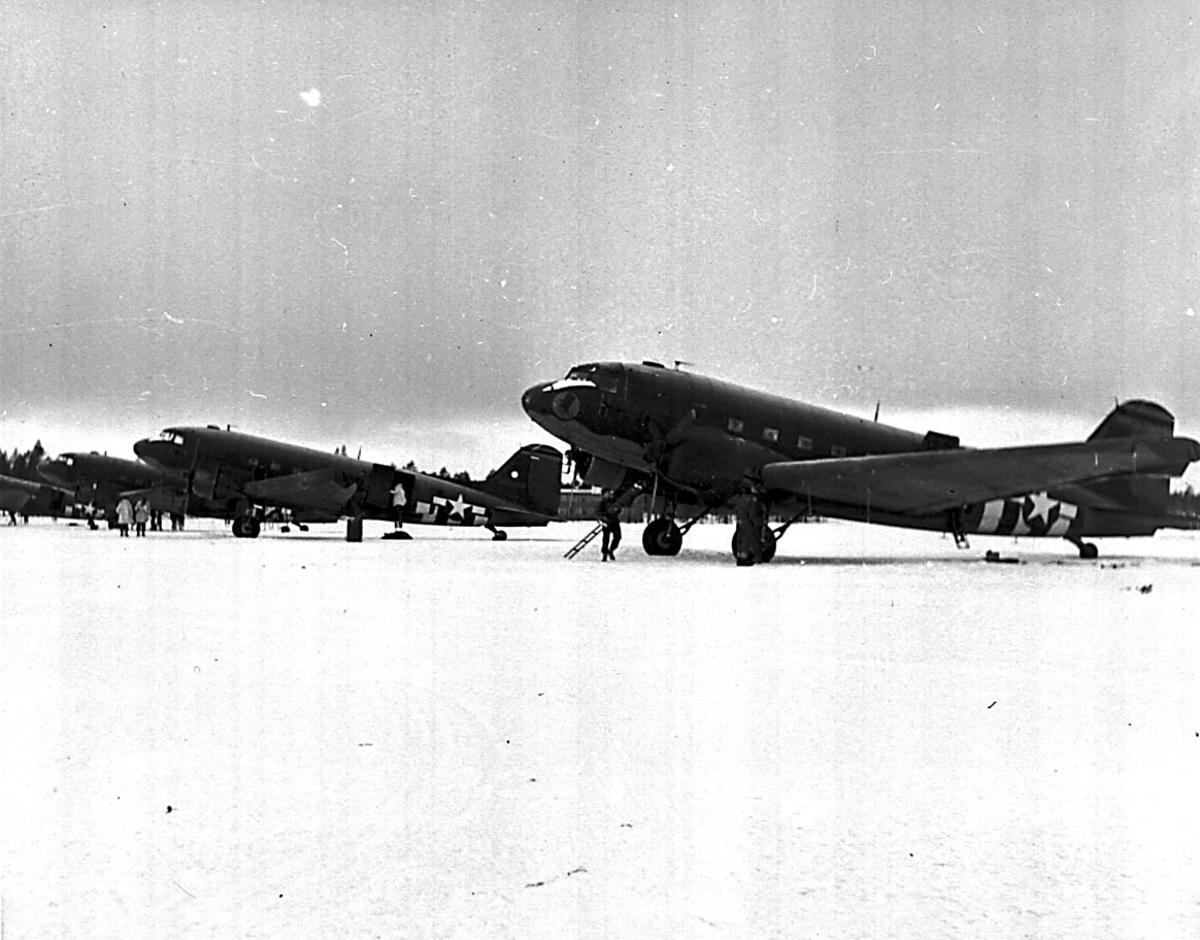 4 fly på bakken, Douglas DC-3/ C-47 Dacota fra USAF. Flere personer ved flyene.