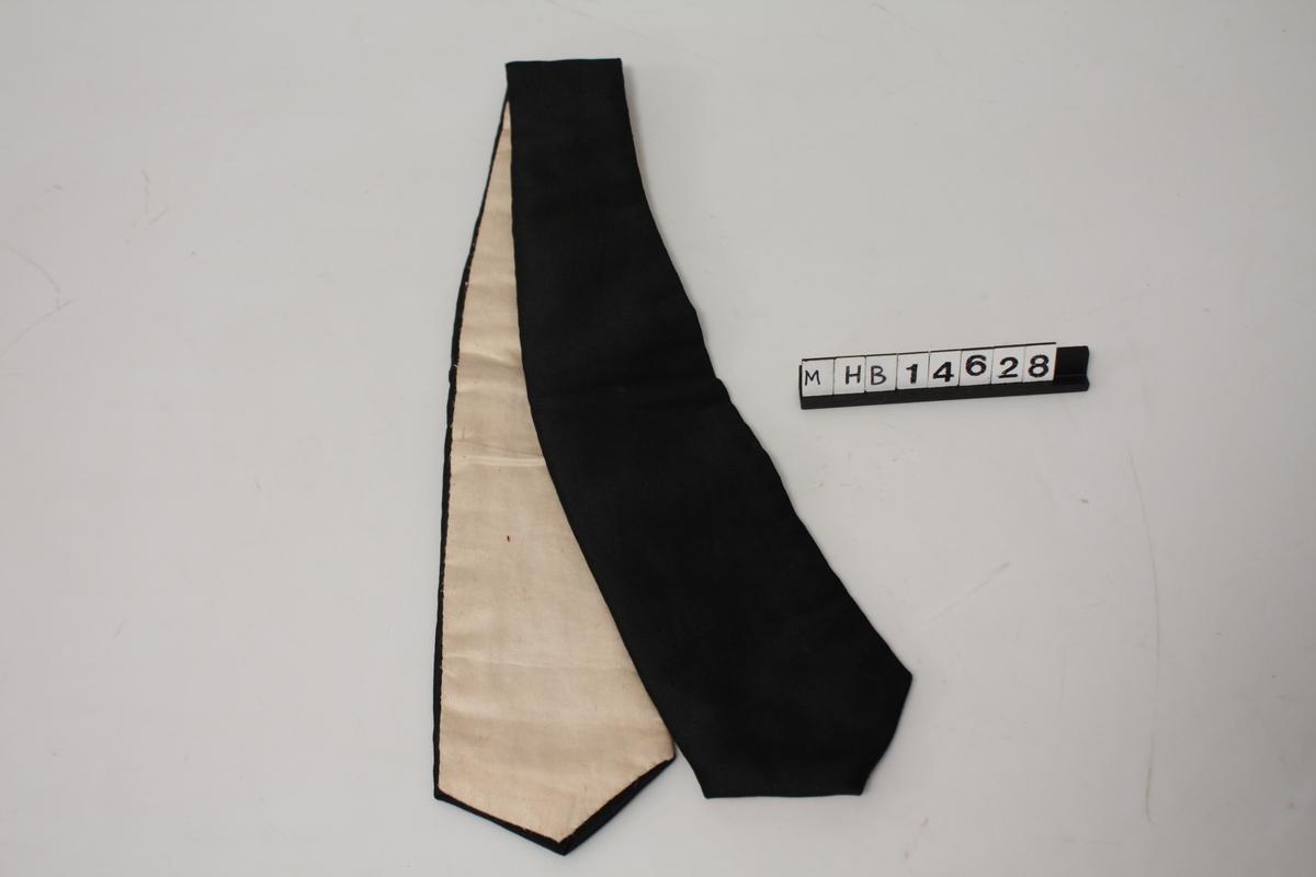Del til drakt i silke-liknende tekstil, sort og hvit. Foret.