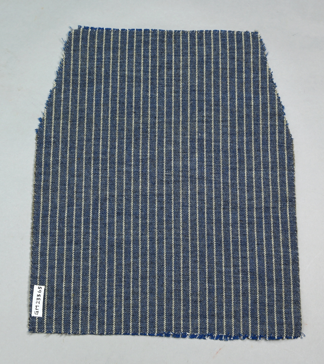 Lapp av kypertvevd stoff med stripemønster. Bomullsrenning, innslag ull. Sidene er kastet over.