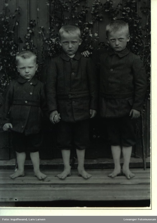 Gruppebilde av tre barbeinte brødre.