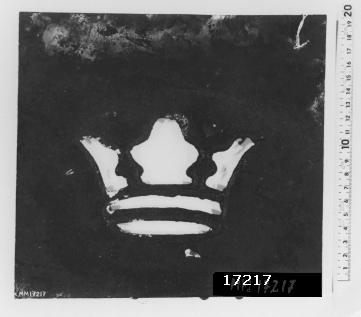 Fyrkantig plastskiva med en utskuren öppen krona i mitten, cirka H = 90 mm, B = 130 mm. Skivan är på båda sidor täckt med svart färg.