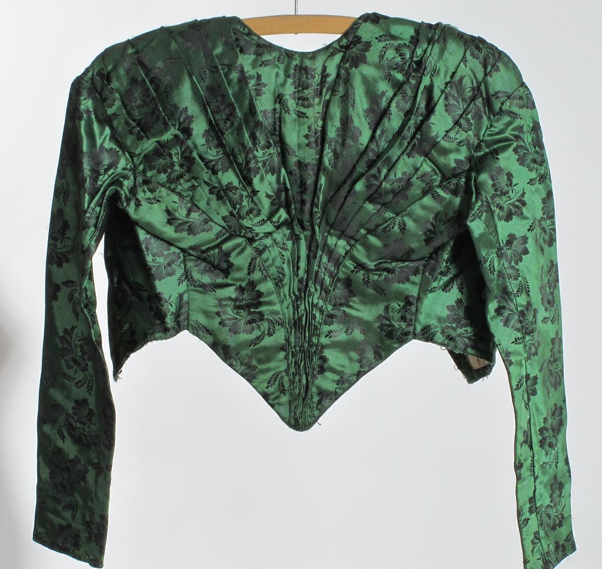 Kjole fra 1880-årene, omsydd antagelig under krigen 1940-45. eller etter denne. Smaragdgrønn silke med sorte ivevde blomster.    a) Overdel, Forstykker med  buede sømmer og legg fra skuldrene til  spiss i livet. Bak knappet med hekter,  foret med lerret. Lange smale ermer.  Splitt midt foran og to bak..   b) Skjørt. Ett rynket til smal linning,  som har blonde pi baks. forholdsvis liten  vidde, omsydd, To brede selelignende  overstykker sydd til.       c) Vest med trykk knapper i forkant, sort for  om ermeåpninger og hals.  d) Stort firkantet stoffstykke, antag. klippet  av det opprinnelige skjørtet. 103x97.    e) Et smalt, uregelmessig stykke stoff, avklippet.  IL. 5 8.