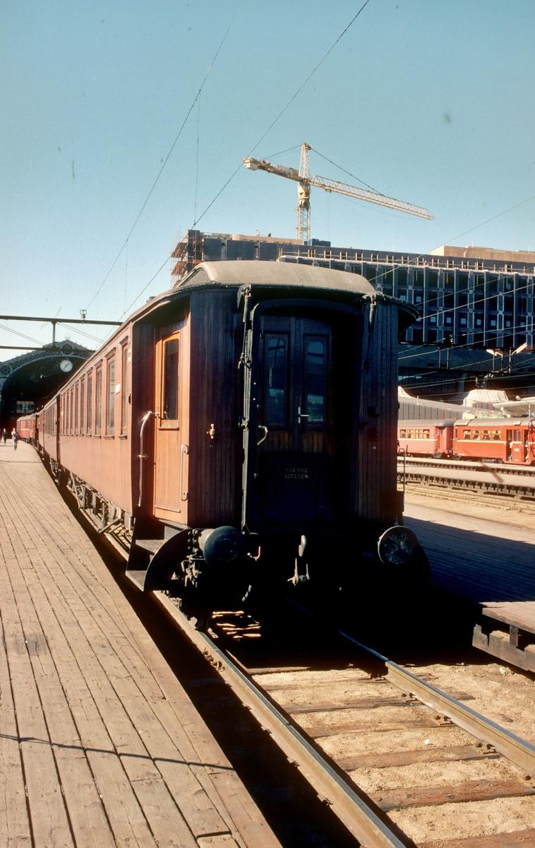Trevogner på Oslo Ø. Togstammen til tog 207 til Gjøvik er skiftet på plass, og avventer lokomotivet som kommer fra Lodalen. I bakgrunnen sees det nye distriktsadministrasjonsbygget (DA-bygget) til NSB, og et motorvognsett type 65c.