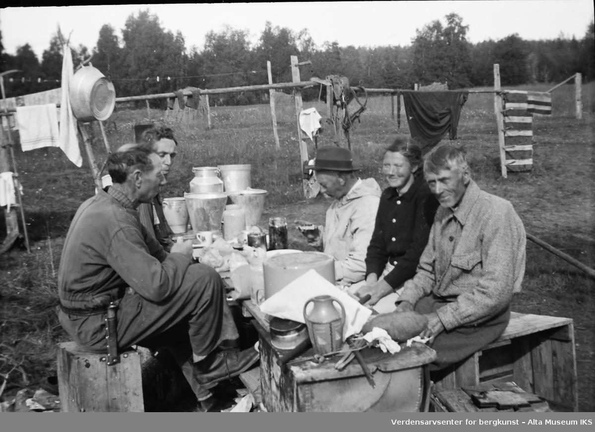 Ole Roald Jøraholmen (Nærmest til venstre) sitter ved et improvisert bord med fire andre. De sitter på kasser.