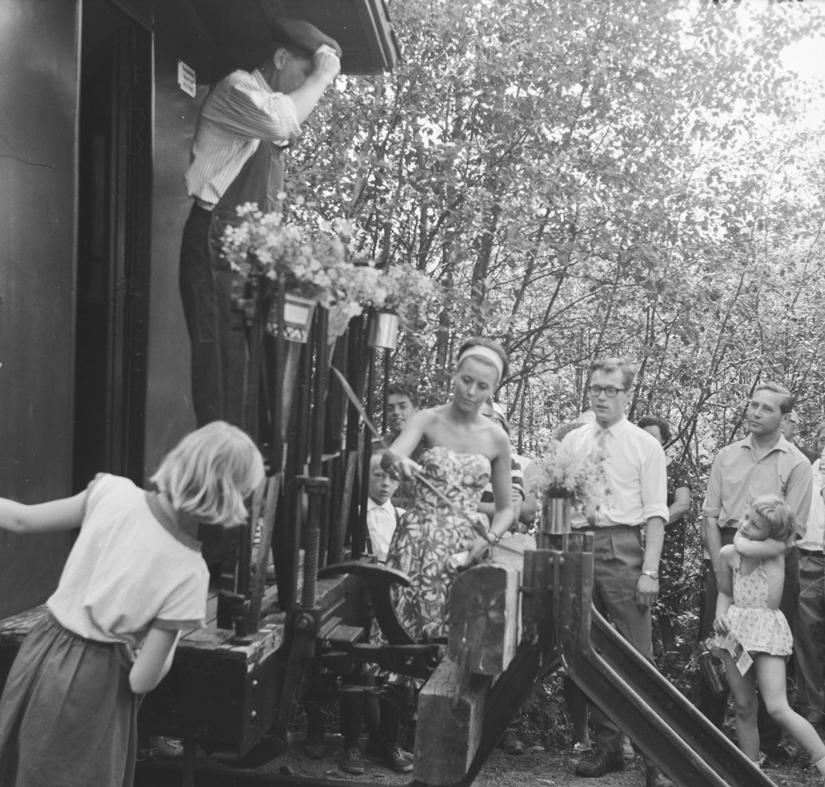 Åpning av museumsbanen 19. juni 1966. Margrethe Wiegels klipper snoren. På plattformen A/L Hølandsbanens formann Preben T. Hysing
