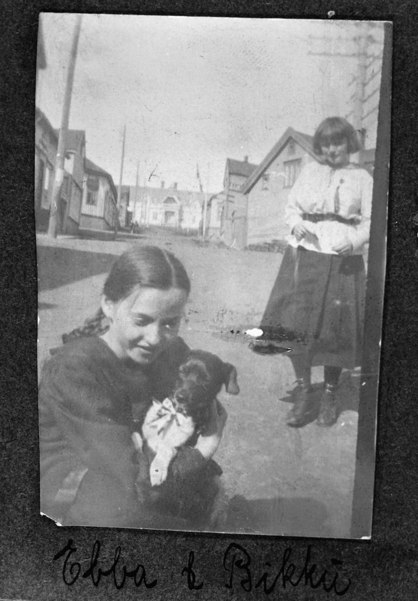 Ung jente, Ebba, leker med hunden Rikki på gatan trolig i Vadsø. Hunden har sløyfe på seg. Bilder er tatt på sommerhalvåret.