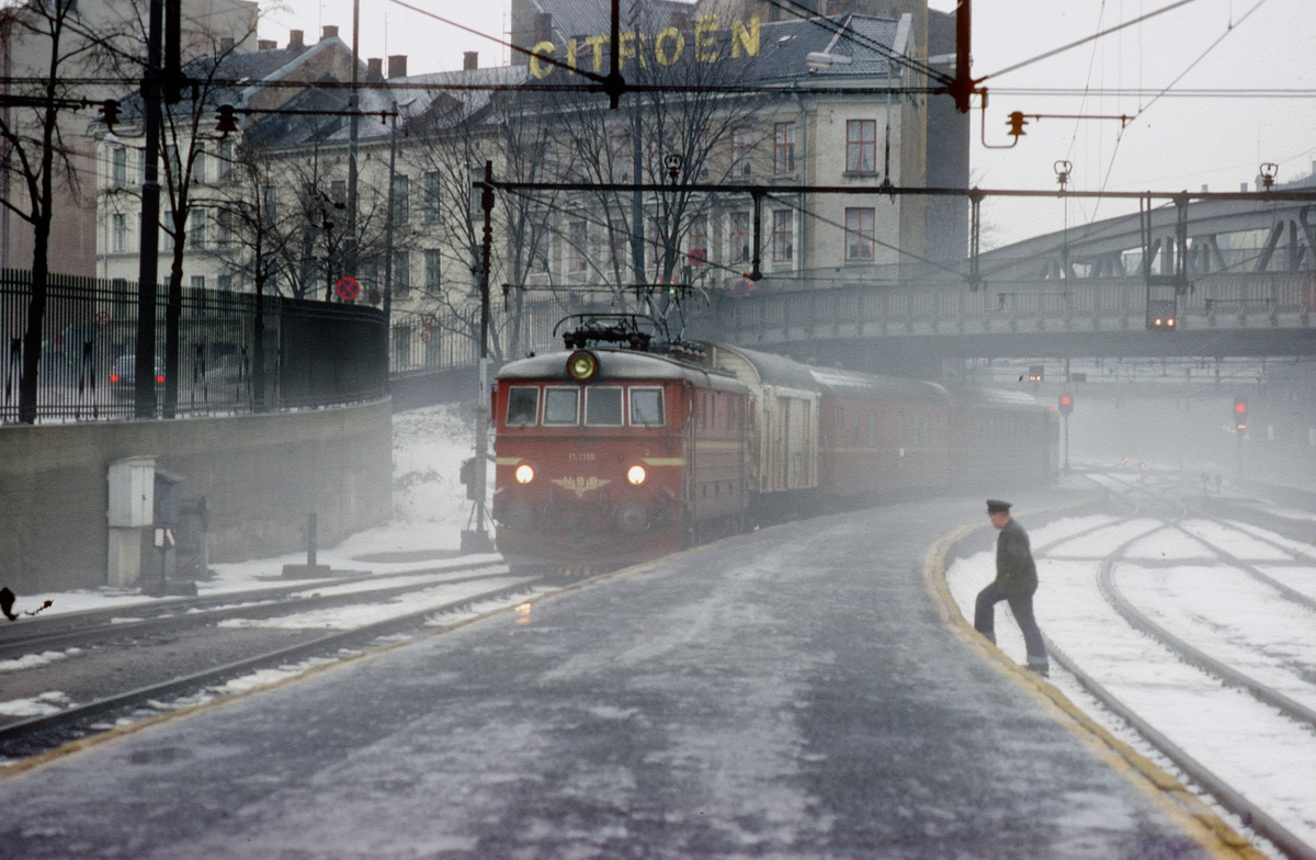 Persontog med NSB elektrisk lokomotiv El 11 2110 ankommer Oslo V en tåkete desemberdag.