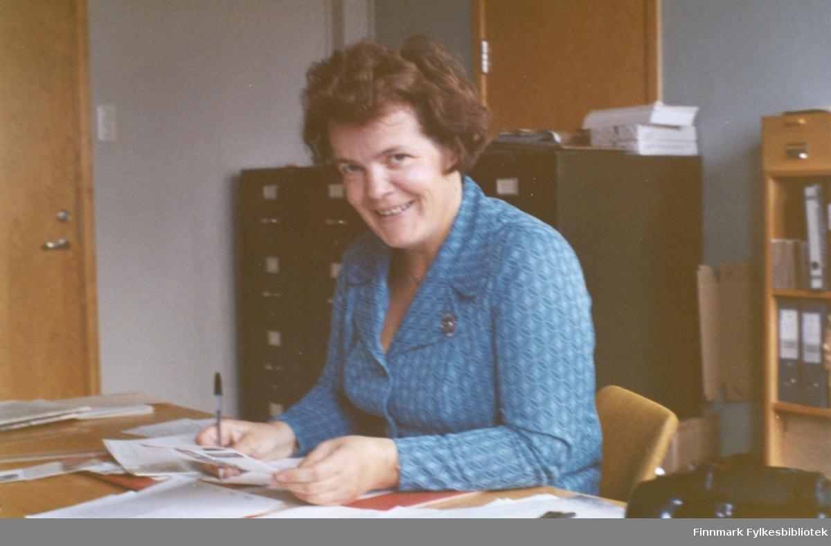Ragnhild Ebeltoft på fylkesskattekontoret i Vadsø ca. 1973-1974. Ragnhild var ansatt ved fylkesskattekontoret i perioden 1951-1993. Bak henne ser vi arkivskap og permer i en bokhylle