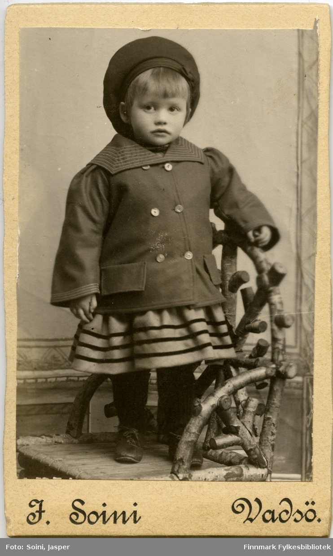 Visitkort. Portrett fra en liten jente, Anna. Hun står på en stol laget av bjørkekvister (dette stol bruker Soini ofte i sine portrettbilder). På dette bildet er hun kledd i en jakke og lue.