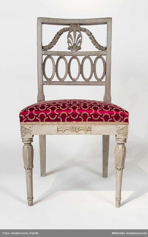 """Stol, sengustaviansk, s.k.""""Nollstol"""". Öppen rektangulär rygg, som avdelas i mitten av en horisontell regel. I ryggens övre del en oval medaljong med fem fjädrar. På ömse sidor tunga S-formade lagerfestoner. I den undre sektionen fem ovaler eller """"nollor"""" efter vilket stolen har fått sitt namn. Överkragade ben och skurna romber vid hörnen och ett rektangulärt fält vid mitten av sargen. Tillverkad ca 1800.Bläcksignerad: """"Dessa stolar förfärdigas af Johannes Anders Son i Lindome By"""". Målad i vit lackfärg med ornament i bronstinktur. Stolen har ursprungligen varit gråmålad.Inköpt på Bukowskis i Stockholm.Stolen (med föremålsnummer 00001-2) har fått sin grå originalfärg framtagen.  Bläcksignerad: """"Dessa stolar förfärdigas af Johannes Anders Son i Lindome By"""". Se ovan för övrig beskrivning.Något sliten."""