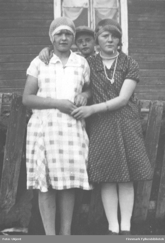 Gruppeportrett at to jenter som poserer i kjoler og tidsriktige hodeplagg fra 20-30.årene. En litt yngre gutt titter over skulderen på jentene. Jenta til høyre har perlekjede om halsen. Navn ukjent. Muligens tatt i Vadsø.
