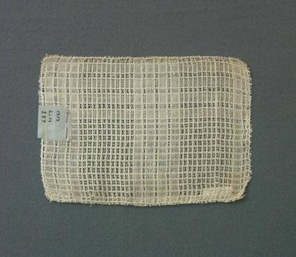 Prov till gardin vävd i tuskaft och stramaljbindning. Provet har bomullsgarn i varp och inslag.Ytterligare prov och vissa vävuppgifter finns i pärm gardiner B, litt B 289.