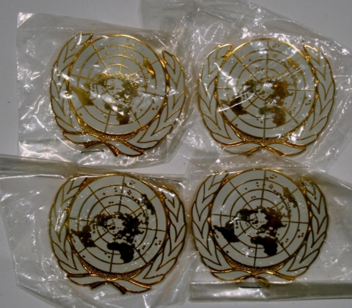 Merke med FN-motiv i forgylt og hvit emalje med nål på baksiden.