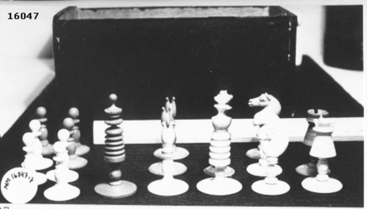 Utskuren schackpjäs,rött torn, som står på cirkelrund fot.