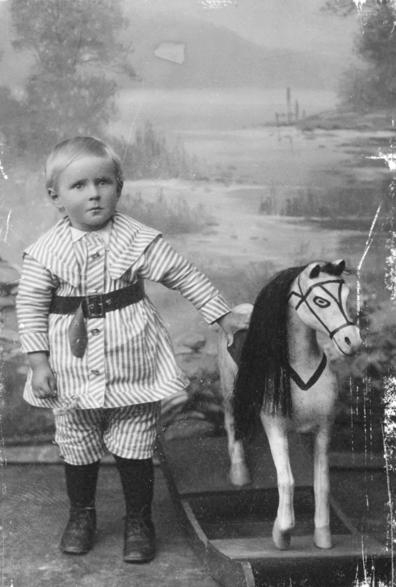 Portrett fra Godtfred Pedersen fotografet hos Emilie Henriksen. På bildet er han ca 2-3 år gammel.Ved siden av han står en gyngehest.
