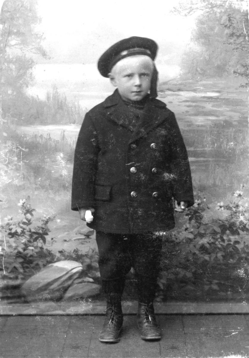 Portrett fra Godtfred Pedersen fotografet hos Emilie Henriksen. På bildet er han 5 år gammel. Han har jakke, lue og skoan på seg.