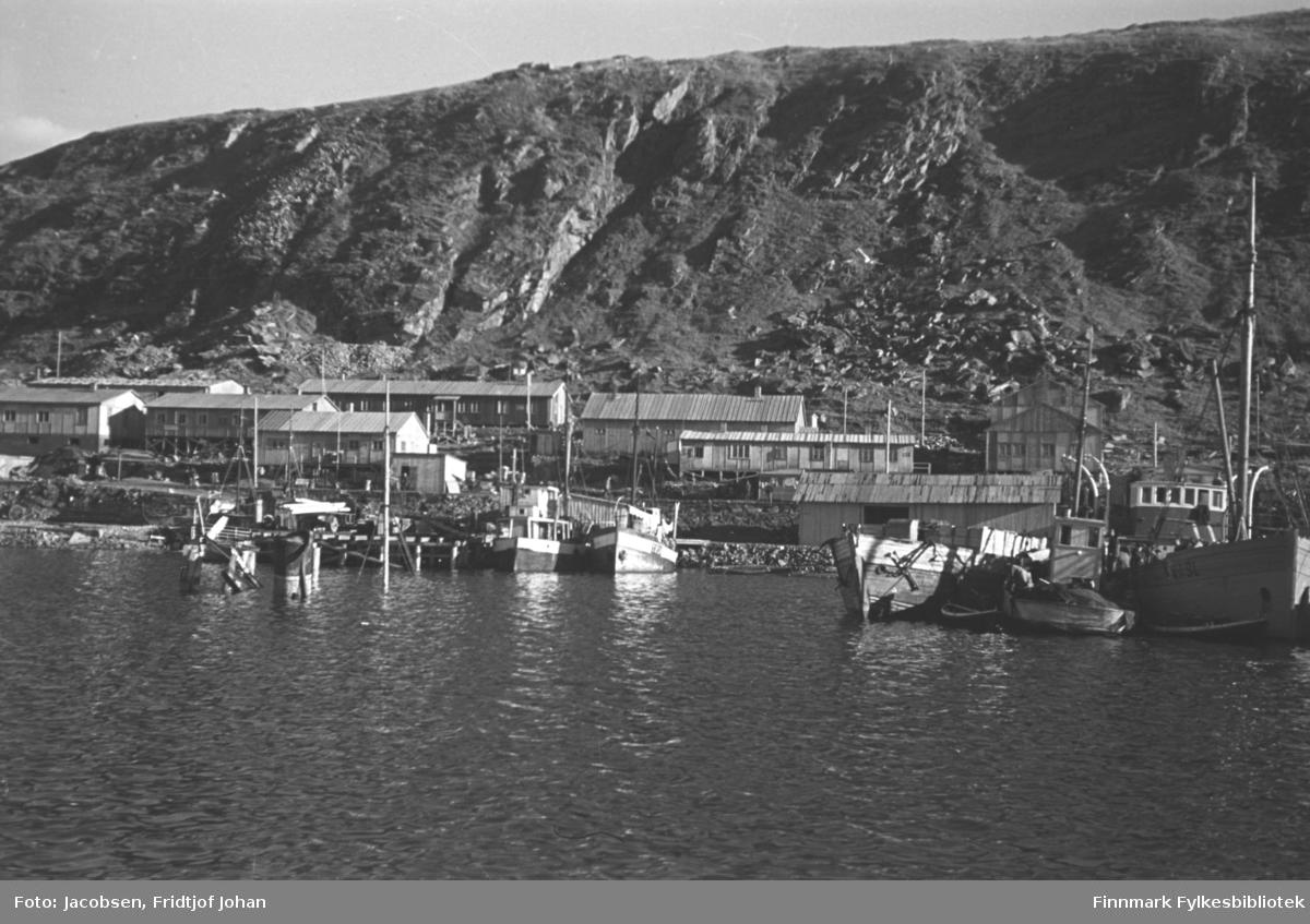 Bilde av Hammerfest havn sett fra sjøen. En del fiske- og fraktebåter ligger ved kaiene. I sjøen nede til venstre på bildet ses skorsteinen og mastene til FFR-båten Brynilen som ble senket ved Dampskipskaia under krigen. En del avlange brakker står på området og flere el-stolper står langs strandkanten. Fjellet i bakgrunnen er Salen.