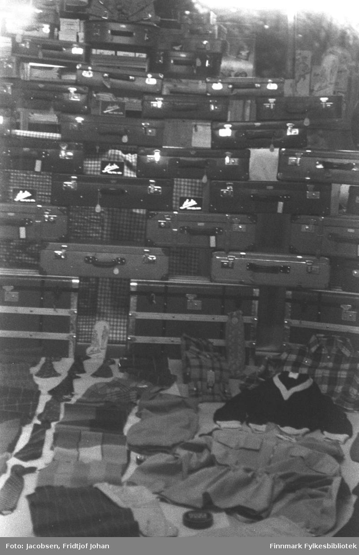 Juleutstilling hos O. Engstad i Hammerfest. En stor stabel med kofferter er utstilt bak på bildet og noen klær og slips ligger på bordet foran på bildet.