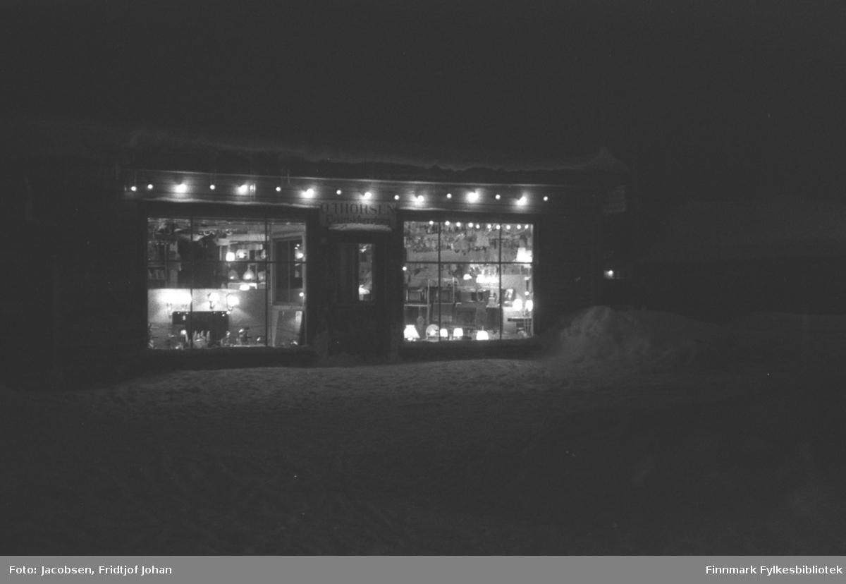 Julestemning i elektroforretningen til O. Thorsen i Hammerfest. En del snø ligger i gaten og på taket til butikken og små brøytekanter ses i veikanten. Mange lamper og småelektrisk er utstilt i vinduene og på bord og hyller inne i forretningen.