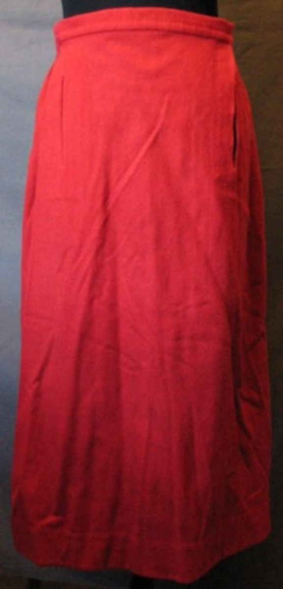 Röd ylleknäppa, sydd i tre våder lättvalkat tyg, kypertvävt. Skodd med röd, blå och vitrutigt bomullstyg 35 mm, 2 mm från nederkanten. Tätt rynkad bak, slät fram. Sprund 235 mm i vänster sida, i höger sida en infälld ficka 90 mm från ovankanten, 130 mm's öppning. Sprundet förstärkt med halvlinnetyg, fickan sydd i samma. Sprundet stängs med sex hakar, handsydda hyskor. Baktill tre hyskor för knäppning med livstycket, 30 mm mellan varje. Oblekt band för upphängning längs med linningen, 90 mm's öglor (nästan isönderslitna). Rekonstruerad kjol.
