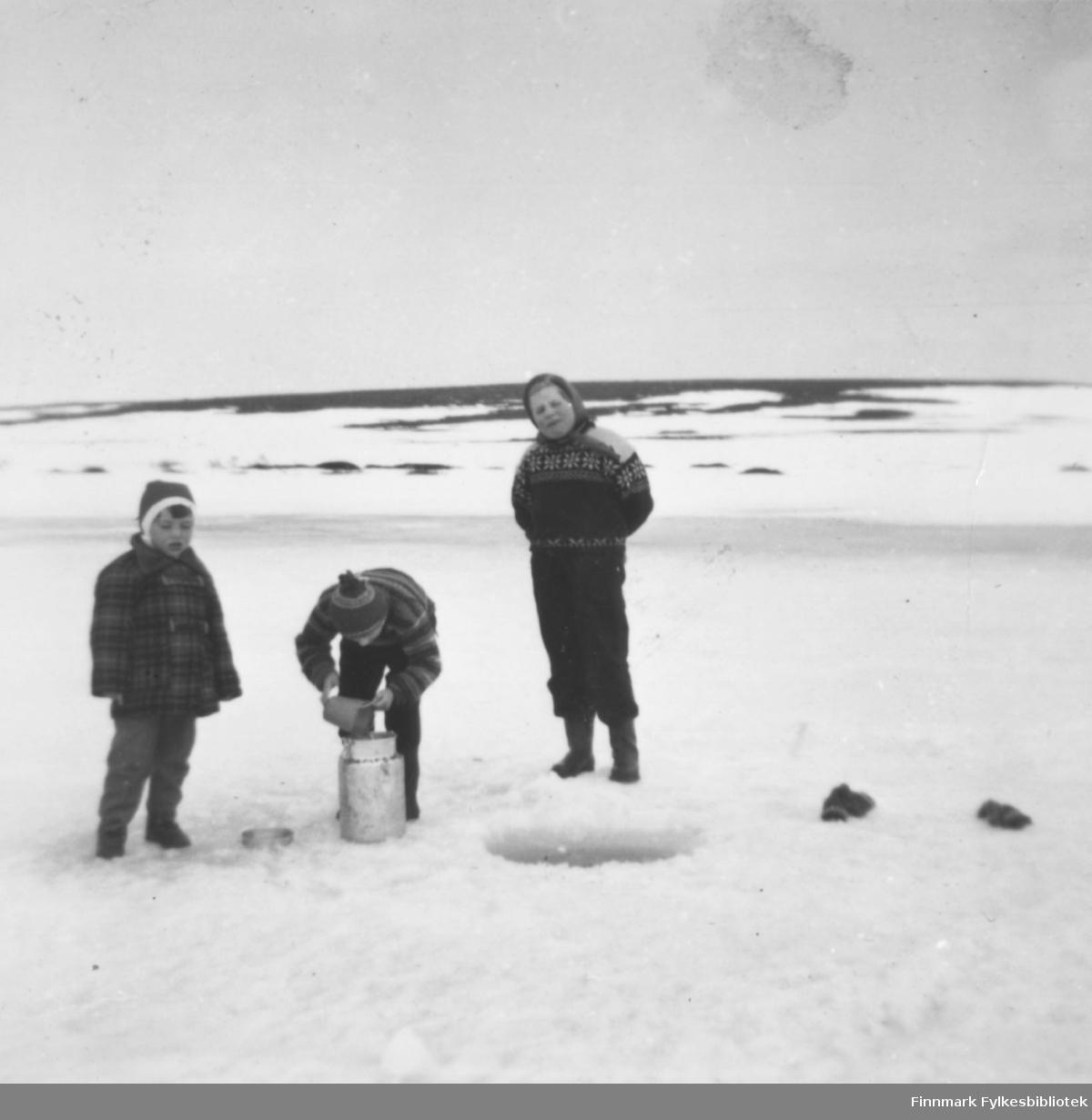 Fra hyttetur ved Valavannet, Vadsø kommune. Fra venstre: Svanhild Rushfeldt (gift Meirud), Inger-Lise Moksnes og Liss Unni Ananiassen. Vannhenting, Inger-Lise med spannet. Votter ligger på isen.