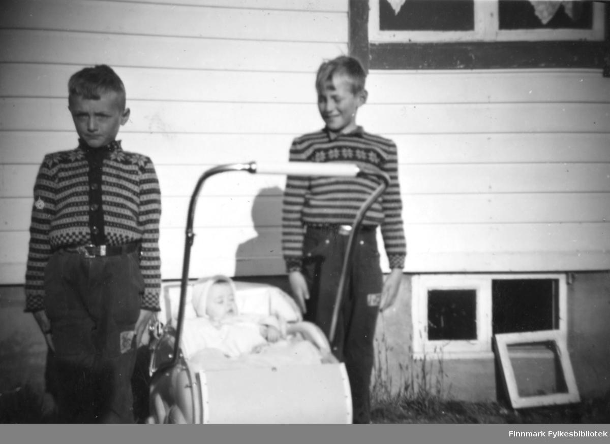 Søsknene Tormod og Svanhild Rushfeldt poserer sammen med onkelen Helge Rystrøm. Svanhild sover i barnevogna med kyse, gutta i stram giv akt kledd i strikkegensere foran et gjenreisningshus med liggende panel. Et kjellervindu står på bakken ved siden av åpningen. Pent vær med sol.