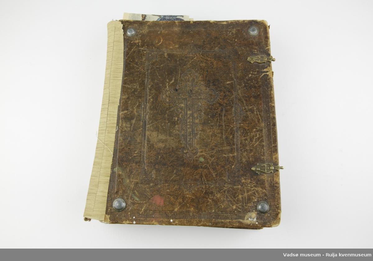 Finsk bibel fra 1893. Skinnkledde permer, preget dekor, bl.a. kors inni ramme. Ryggen er forsterket med et pålimt tapetlignende materiale. Runde metallbeslag i hvert hjørne både foran og bak på boka. Låseanordning av metall i ytterpermer. Hempene til disse er borte.