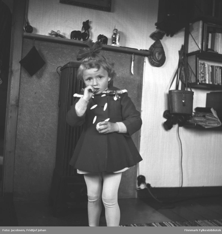 Synnøve Nakken fotografert foran peisen. Hun har en mørk, kort kjole med store, hvite knapper på seg. Under kjolen har hun en lys ullgenser. Hun har også hvit strømpebukse og en mørk sløyfe på hodet. 17. mai-sløyfa henger delvis over skulderen hennes. Oppå peishylla står endel nips og en bokhylle ses til høyre på bildet. Der står mange bøker, noen blader og en kikkertboks henger på siden.