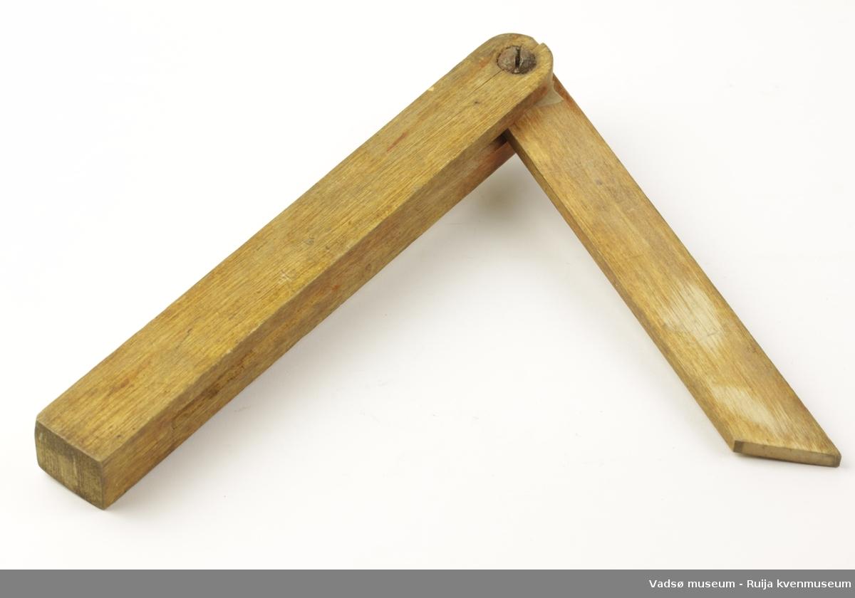 Hjemmelaget vinkelhake i tre i to deler. Avrundet i ene enden, rett avskåret i andre enden. Delene er festet med skrue og vingemutter i metall. Kortsiden av vinkelmålet kan felles inn i langsiden.